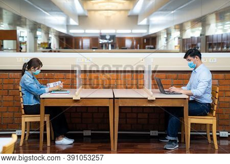Two Asian University Students Wearing Face Mask And Sitting In Library Social Distance From Other 6