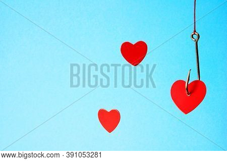 Heart On A Hook On A Blue Background. A Metal Fishhook Hanging From A Rope Pierced The Red Cardboard