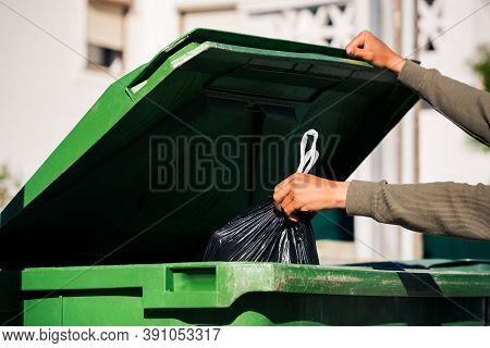 Man Throwing Out Black Eco-friendly Recyclable Trash Bag In To Big Plastic Green Garbage Container.