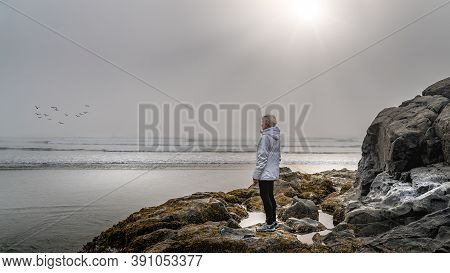 Senior Woman Looking Out Into The Dense Fog Over The Pacific Ocean In Cox Bay At The Pacific Rim Nat