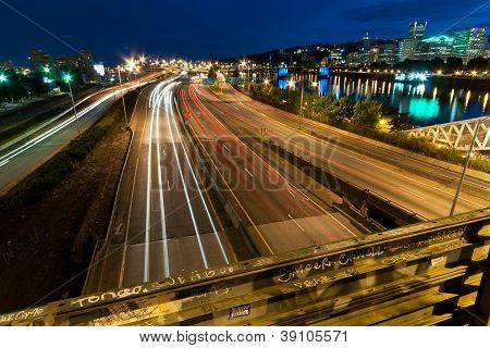 Traffic headlights streak down the I-5 freeway along the Portland Waterfront at dusk poster
