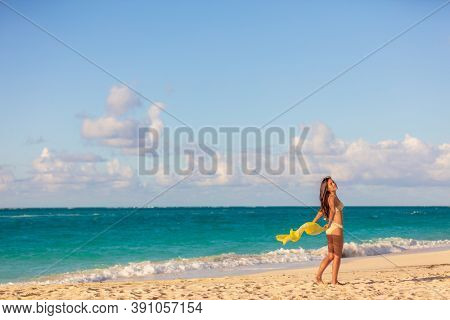 Beach summer travel vacation woman relaxing on Caribbean tropical holidays ocean at sunset. Wellness relaxation spa bikini Asian girl with beachwear sarong free in the wind.