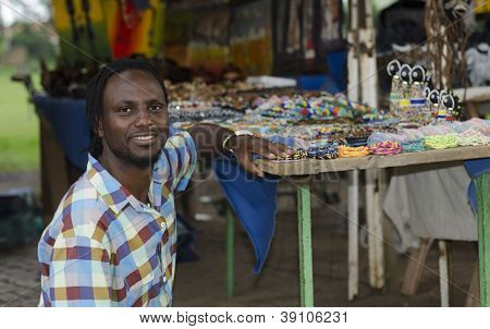 African Curio Salesman In Front Of Ethnic Items