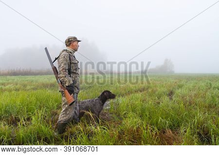 The Hunter And His Dog Went Out On A Damp Meadow On A Foggy Morning To Hunt