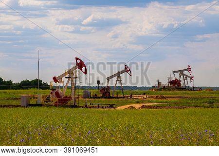 Oil Drilling Derricks And Pump Jack. Oil Drilling Derricks At Desert Oilfield For Fossil Fuels Outpu