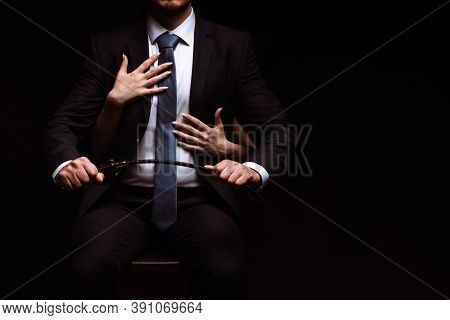 Businessman Man In A Dominant Suit With A Leather Whip Is Sitting In A Chair. Submissive Girl Puts H