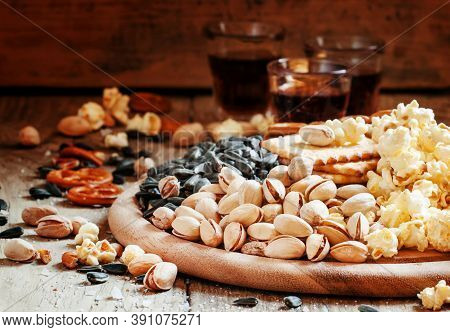 Salted Pistachios, Popcorn And Other Salty Snacks On A Wooden Platter, Selective Focus