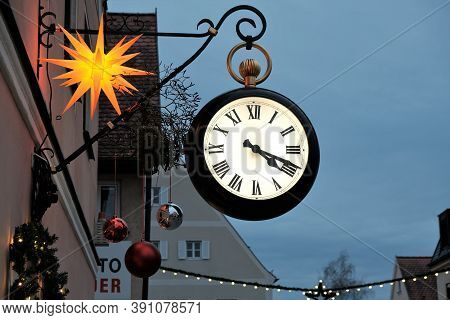 Christmas Time In Europe. Round Clock And Christmas Street Decor On Festive Christmas Town Blurred B