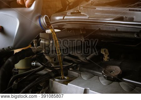 Mechanic In Service To Repair The Car, Refueling And Pouring From Bottle To Change Lubricant Oil At