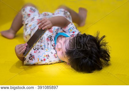 Boy Is Lying Down Looking At Mobile Screen. Children Are Addicted To Mobile Phones. Child Watch The