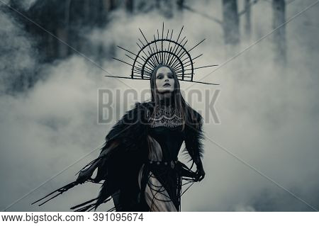 Young Woman In Image Of Witch Stands In Black Dress And Crown On Her Head In Dark And Foggy Forest.