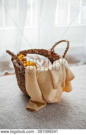 Wicker Basket With Linen. Knitted Sweaters In A Wicker Basket In The Interior. Cozy Autumn.