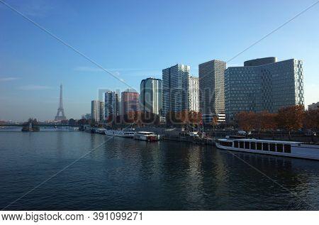 Paris, France - November 21, 2018: Seine river, Eiffel tower, port de Javel and moderm tall buildings district under blue sky