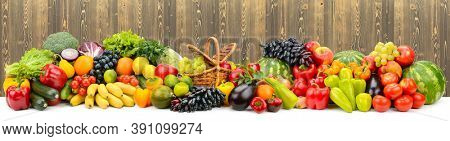 Panoramic collage of ripe, juicy fruits, berries and vegetables on wooden background.