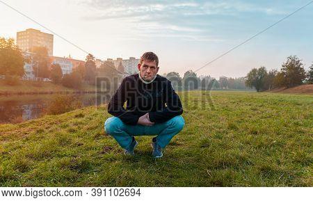 Portrait Of Pensive Young Caucasian Man Sitting In Autumn Landscape Near Vltava River, Ceske Budejov