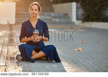 Attractive Woman In Blue Dress Sitting On Ground. Spare Time On Nature. Take Break And Coffee Time C
