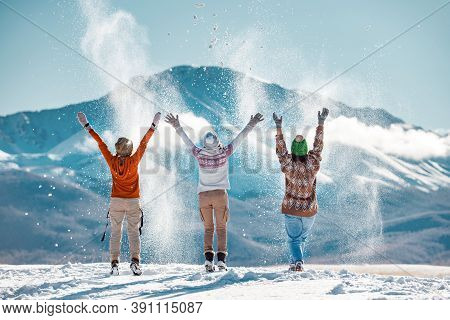 Three Happy Adult Girls Are Having Fun And Throws First Snow On Background Of Mountains. Travel In W