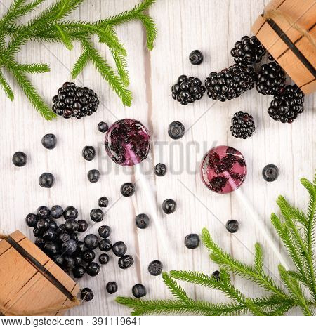 Homemade Lollipops Made From Natural Dehydrated Bilberry And Blackberries On A White Wooden Backgrou