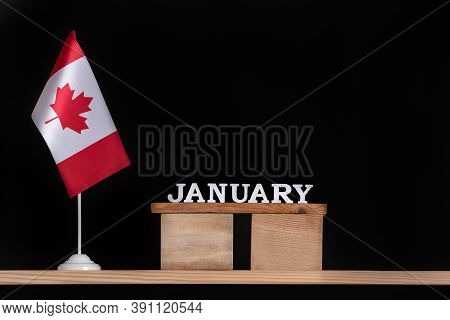 Wooden Calendar Of January With Canadian Flag On Black Background. Holidays Of Canada In January.