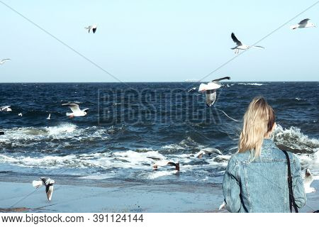 The Blonde Girl Looks At The Ocean. Stormy Sea, Ocean And Background Many Seagulls Soar In The Sky.