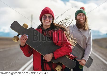 Two Cheerful Girls Stands With Long Boards And Having Fun At The Mountain Road