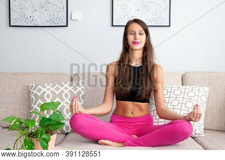 A Young, Happy, Smiling Woman Is Doing A Yoga Meditation, Asana - Relaxing At The Cozy Home. The Hea