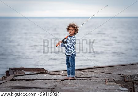 Cute Curly-haired Kid Fisherman Stand On Concrete Pier With A Vintage Fly-fishing Rod And Reel. Summ