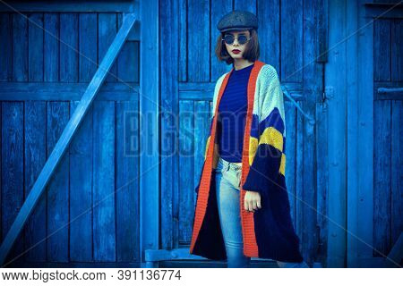 Portrait of a modern girl by blue old wooden gates. Fashion model, autumn style.