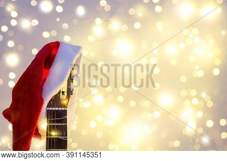 Acoustic Guitar With Red Santa Hat And Light Garland. Christmas Music Song Concept With Copyspace