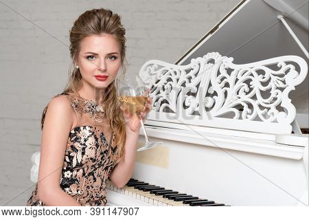 Elegant Blonde Lady With Glass Of Wine Sitting Near White Grand Piano In A Luxury Classic Interior.