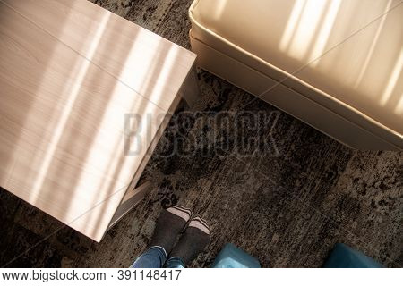 Young Person Feet In Socks Stand Near Contemporary Empty Wooden Table And Soft White Pouf On Pattern