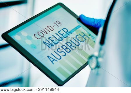 closeup of a doctor man, wearing blue surgical gloves, having a digital tablet in his hands with the text covid-19 new outbreak written in german in its screen