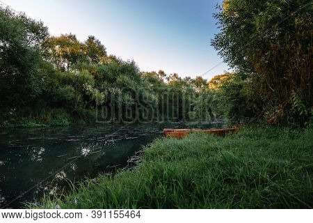 Calm Water Flow, Morning Fog And Wooden Boat. Summer Or Autumn Sunrise Over The River. Natural Beaut