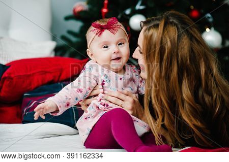 Baby Girl With Mom On Bed In Bedroom Near Christmas Tree. Happy New Year And Merry Christmas. Christ
