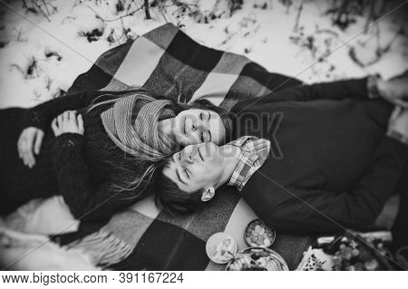Man And Girl Is Lying On A Blanket At The Winter Picnic On The Valentines Day In A Snowy Park, Fores