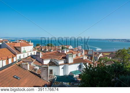 Lisbon And Tagus River View Of The Streets And The Orange Roofs Of The Old Town.