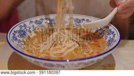 Woman eat chinese Sichuan Dan Dan Noodles
