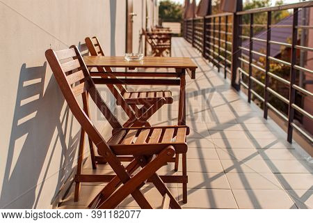 Sunlight And Table And Chairs In Modern Balcony. Inside Balcony View In Sunlight And Shadow