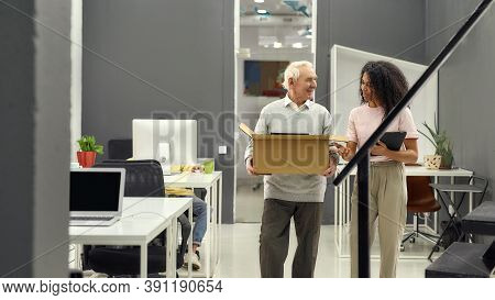 Friendly Female Company Executive Welcoming New Employee Aged Man, Senior Intern Holding Box With Be