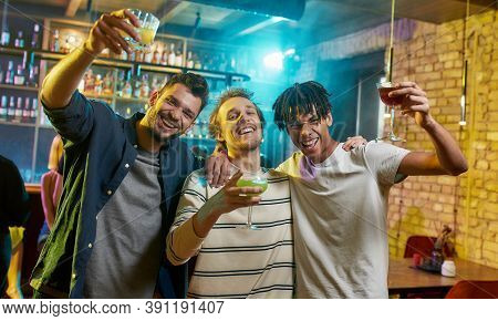Meet Friends Tonight. Cheerful Young Men Looking At Camera, Posing With Cocktail In Their Hands. Fri
