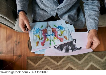 Top View Of Psychologist Choosing Picture With Ink Stain. Rorschach Inkblot During Therapy Session.