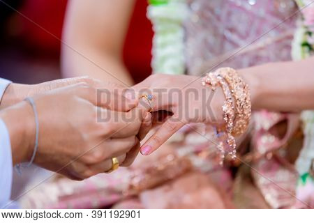 Wedding Rings. He Put The Wedding Ring On Her. Close Up Groom Put The Ring On Bride. Thai Wedding Ce