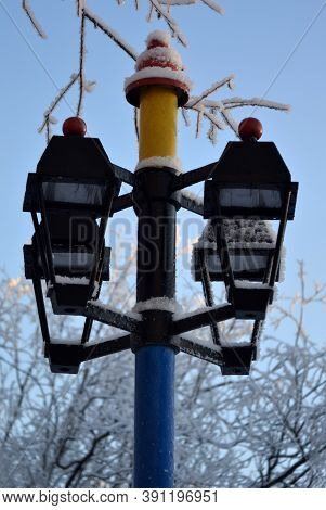 Snow-covered Lampposts In The Park In The Middle Of Winter Polar Region Against The Blue Sky