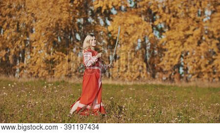 Militant Woman Runs On Autumn Field With Sword