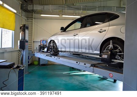Grey Car Mounted On A Stand For Adjusting Camber-convergence With Sensors On Wheels
