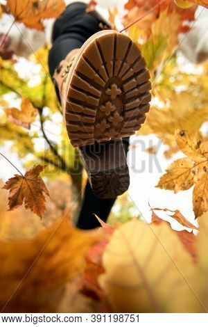 Close-up Of A Woman Foot In Boots, Walking On Autumn Leaves. Playing With Dry Leaves. Autumn Outdoor