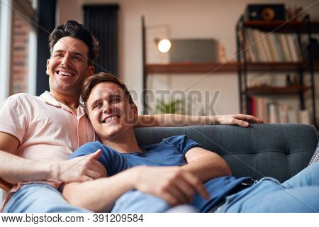 Loving Same Sex Male Couple Lying On Sofa At Home Watching TV And Relaxing Together