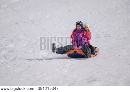Two Happy Active Kids Delightful Girls Riding Tube On Snow Slope During Winter Mountain Resort Activ
