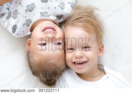 Three Little Smiling Kids Play Together On Bed. Happy Brother And Sister Show Emotions. Twins Have F