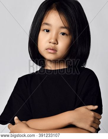 Portrait Of Nice Calm Asian Korean Kid Girl In Black T-shirt And With Bob Hairstyle Looking At Camer